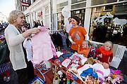 Een vrouw kijkt naar wat koopwaar op de vrijmarkt in Utrecht tijdens Koninginnedag 2012.<br /> <br /> People are selling stuff at the flee market on Queensday in Utrecht.