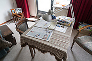 table with newspaper and reading glasses at the home of an elderly person