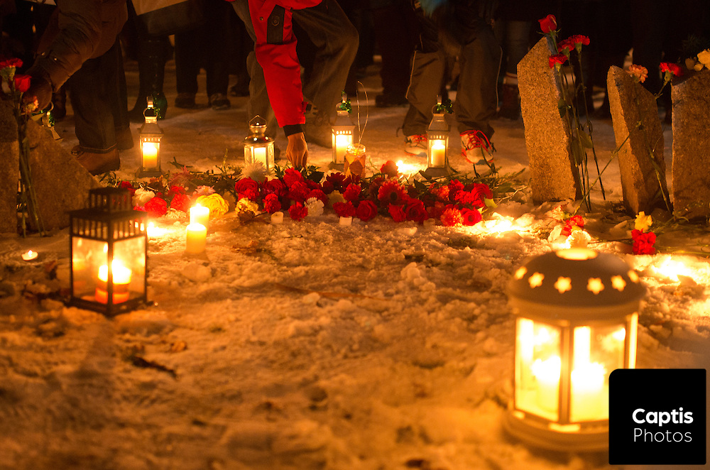 People place roses in front of the Women's Memorial in Minto Park during the vigil. December 6, 2014.