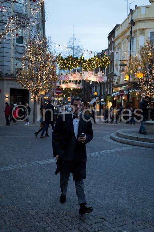 A man wearing a bow tie walks through Seven Dials near Covent Garden, on 12th December 2017, in London England.