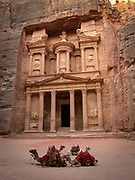 "Low angle view of the Treasury, a facade carved out of stone by the Nabataeans. Currently one of the ""Seven Wonders of the World"" Camels in the foreground."