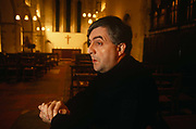 Father Peter Geldard sits in his former Anglican Church near Faversham, England. He sits in a pew clasping his hands together and looking away as if lost in thought, the Christian cross and altar in the distance. Geldard is known for his stance against the Church of England's vote allowing the ordination of women priests in 1992, causing a huge row with Anglican church worshippers. Clergy, including five bishops, eventually left to join the Catholic Church including Father Geldard, who led the opposition and became a notorious debater, campaigner, and general nuisance to the church. He eventually resigned from his Anglican orders, moved out of his vicarage house and along with thirty-five members of his former parish (including the churchwardens and all the members of the parish council), now attends Mass at the Catholic church in Faversham.