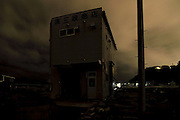 """ISHINOMAKI - Utter Darkness"" shows the neighbourhoods most affected by the tsunami, under minimal light. The town is asleep; the streets dark. Some outlines are visible. The photographs may hint at normalcy, yet a few details remind us of the true situation."