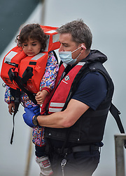 © Licensed to London News Pictures. 12/08/2021. Dover, UK. A child migrant is carried ashore by a Border Force official at Dover Harbour in Kent after crossing the English Channel today. Hundreds of migrants have made the crossing in recent weeks. Photo credit: Stuart Brock/LNP