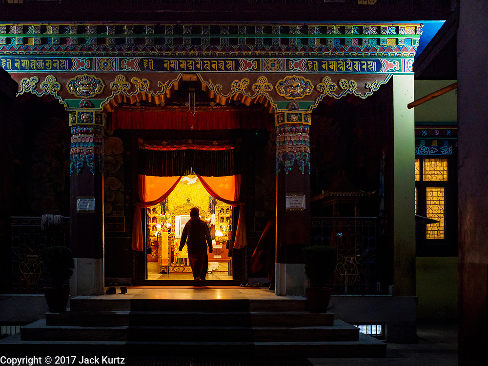 17 MARCH 2017 - KATHMANDU, NEPAL: A Buddhist monk enters the prayer hall of a monastery before morning prayers at Boudhanath Stupa in Kathmandu. There are several Tibetan monasteries around the stupa, which is the holiest site in Nepali Buddhism. It is also the center of the Tibetan exile community in Kathmandu. The Stupa was badly damaged in the 2015 earthquake but was one of the first buildings renovated.     PHOTO BY JACK KURTZ