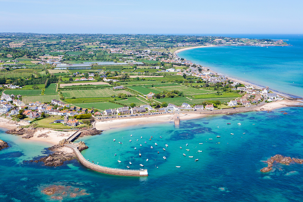 Aerial view of the boats and pier at La Rocque harbour and the east coast with its crystal clear and calm turquoise water in Jersey, Channel Islands