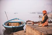 A Hindu Sadhu meditating in the cross-legged lotus position beside the banks of the River Ganges at dawn, River Ganges, Varanasi, India