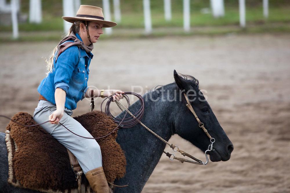 Young Brazilian Gaucha cowgirl female, riding horses, preparing to compete in a rodeo. Gaucho cowboy Rodeo, Flores de Cunha, Rio Grande do Sul.