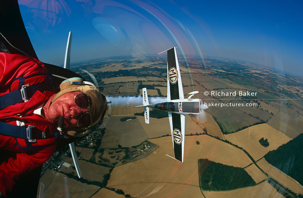 Brian Lecomber flew as a professional aerobatic pilot for 23 years, during which time his Firebird Aerobatics team completed over 2,800 solo and formation displays in front of an estimated total of 90 million spectators. They gave displays in 15 countries, and had a 100% safety record before closing in 2003. They will be remembered as one of the UK's most successful professional civilian aerobatic display company. Lecomber has been a racing motorcycle mechanic; journalist; wing-walker in a flying circus; chief flying instructor in the Caribbean; crop-spray pilot, and then a best-selling author of aviation novels. We see him in-flight performing a tight turn above southern English fields of Buckinghamshire with flying partner Alan Wade when the team was sponsored by the Rover Group.