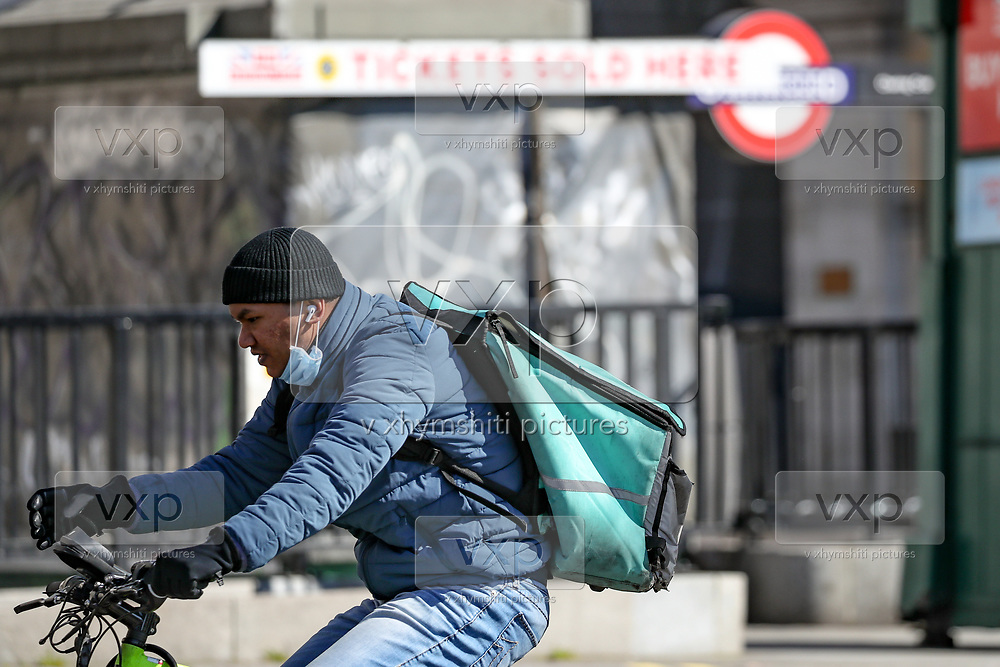 A delivery cyclist is seen wearing face protective mask in London, Wednesday, March 25, 2020. British lawmakers voted to shut down Parliament for one month due to the coronavirus outbreak. (Photo/Vudi Xhymshiti)