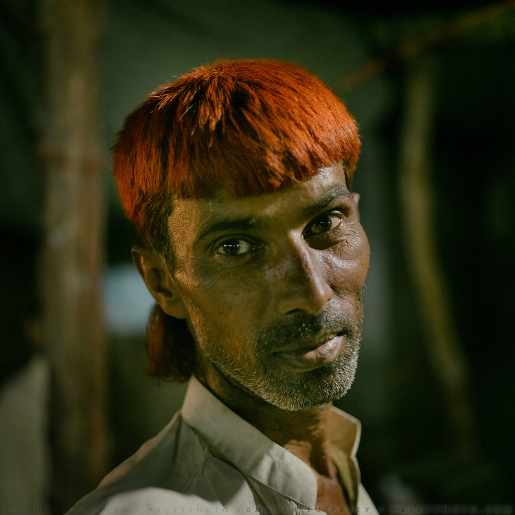 Portrait of man whose hairs have been dyed with henna. In the city of Jacobabad.