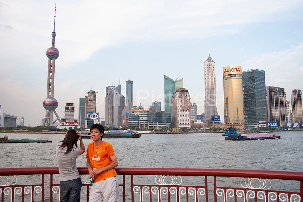 Tourists take pictures on the Bund at sunset in Shanghai, China. Every day at sundown, tourists gather to watch the sun go down and the lights all along the Huang Pu River come to life. The Bunds old western buildings is the most famous in Shanghai, which is known as a city with much French, American Art Deco Russian, and British architecture. The Bund is dominated by the The Hong Kong & Shanghai Banking Corporation Building, the Customs House and the former Bank of Communications.