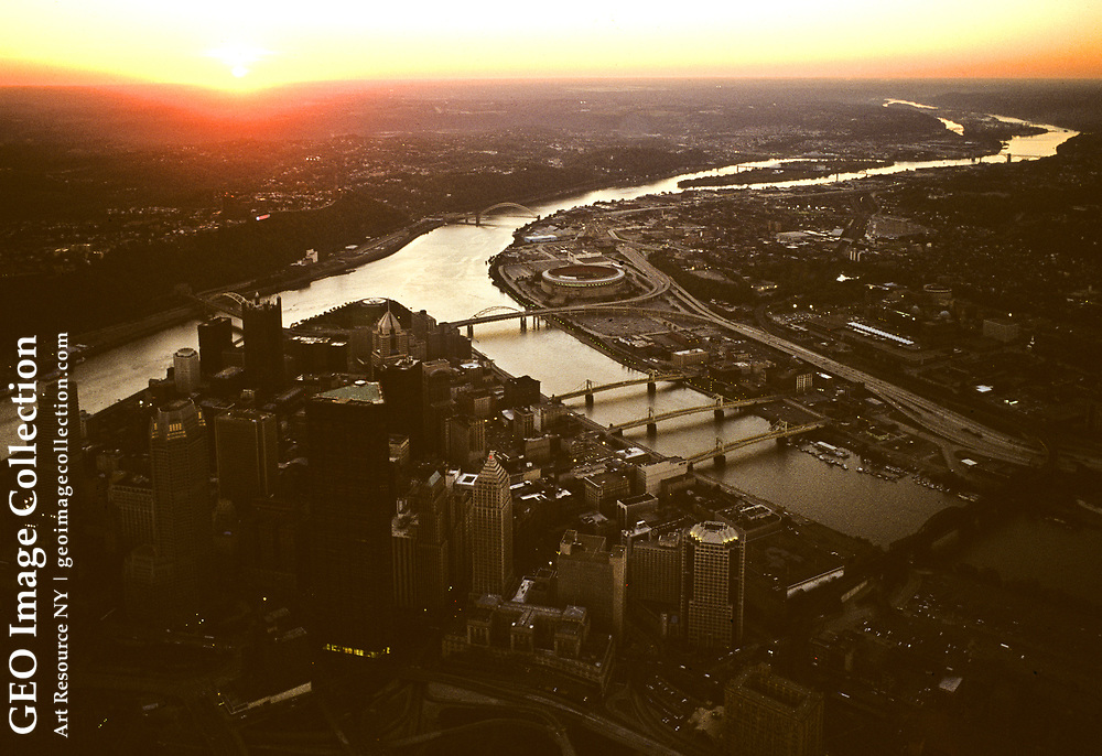 """Aerial views at sunset of the city of Pittsburgh at the confluence of the Allegheny River and the Monongahela River to form the Ohio River. The rivers shape the triangle of downtown Pittsburgh. The business district of downtown Pittsburgh is called the Golden Triangle. Pittsburgh is known as """"The City of Bridges"""" and """"The Steel City"""" for its many bridges and manufacturing history. The seat of Allegheny County, Pittsburgh is regularly rated one of America's cleanest and livable urban cities."""