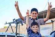 Children hold their two fingers up forming the symbol of Victory as they greet members of the Free Syrian Army (FSA) ahead of a military operation in Minaq (Menagh) military airport on Friday, Jun 29, 2012. (Photo by Vudi Xhymshiti)