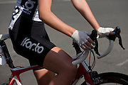 Close-up of a woman cyclist waiting to re-join a road race competition on the streets of Woking.