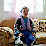 """Portrait of a Small Flower Miao ethnic minority woman, wearing her traditional clothing, in her home Gao Yuan village, Guizhou, China. Almost 35% of Guizhou's population is made up of over 18 different ethnic minorities including the Miao. Each Miao group became isolated in these mountainous regions, hence the present day diversity in their culture, costume and dialects. According to a popular saying, """"if you meet 100 Miaos, you will see 100 costumes."""""""