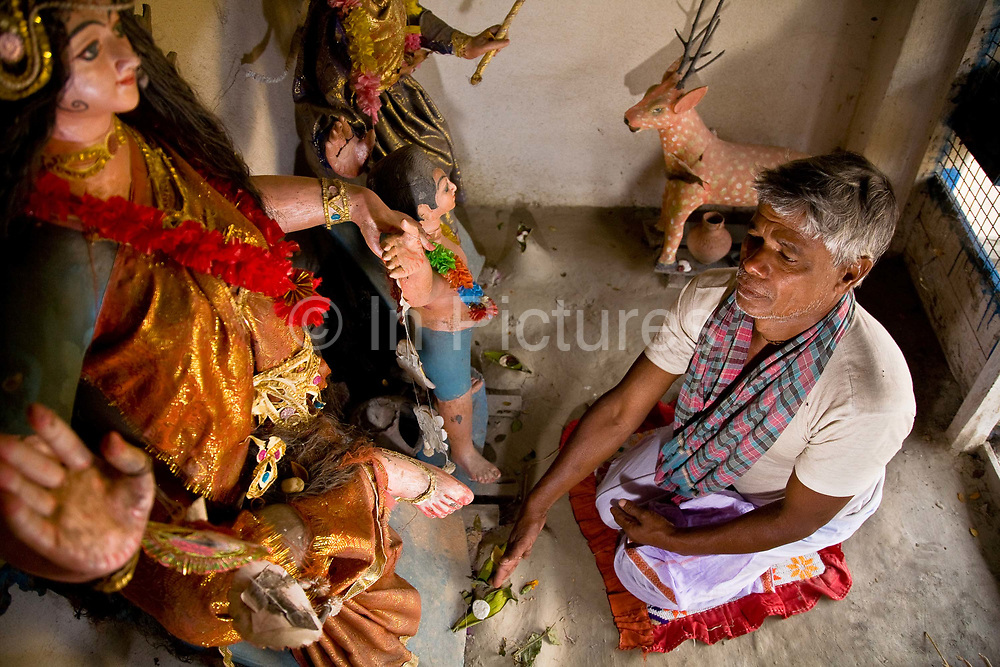 Monindro Mondol prays to Bonobibi, the goddess of the forest. He does this on a daily basis to protect him and his family form being attacked by the Bengal tiger, not an uncommon problem in West Bengal's Sunderbans delta, India
