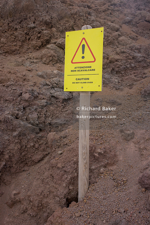 Tourists' warning sign embedded in lava rock at the dormant crater edge of Vesuvius volcano.