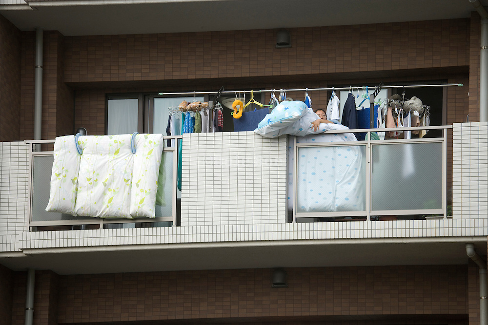 person hanging bedding over the balcony to air it