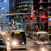 Streetcar and passenger vehicle traffic on Main Street in the evening in downtown Kansas City, Missouri.