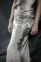 Fashion pictures of a beautiful woman wearing cream satin cocktail sleeveless dress detail