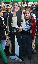 © Licensed to London News Pictures. 16/12/2015. London, UK. A fan stands with a full sized photo of Han Solo in Leicester Square ahead of the UK premiere of Star Wars: The Force Awakens. Photo credit: Peter Macdiarmid/LNP