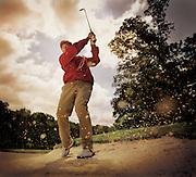 An Asian man takes a golf swing.