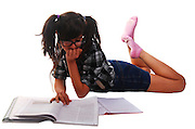 Teen Girl studies while lying on the floor