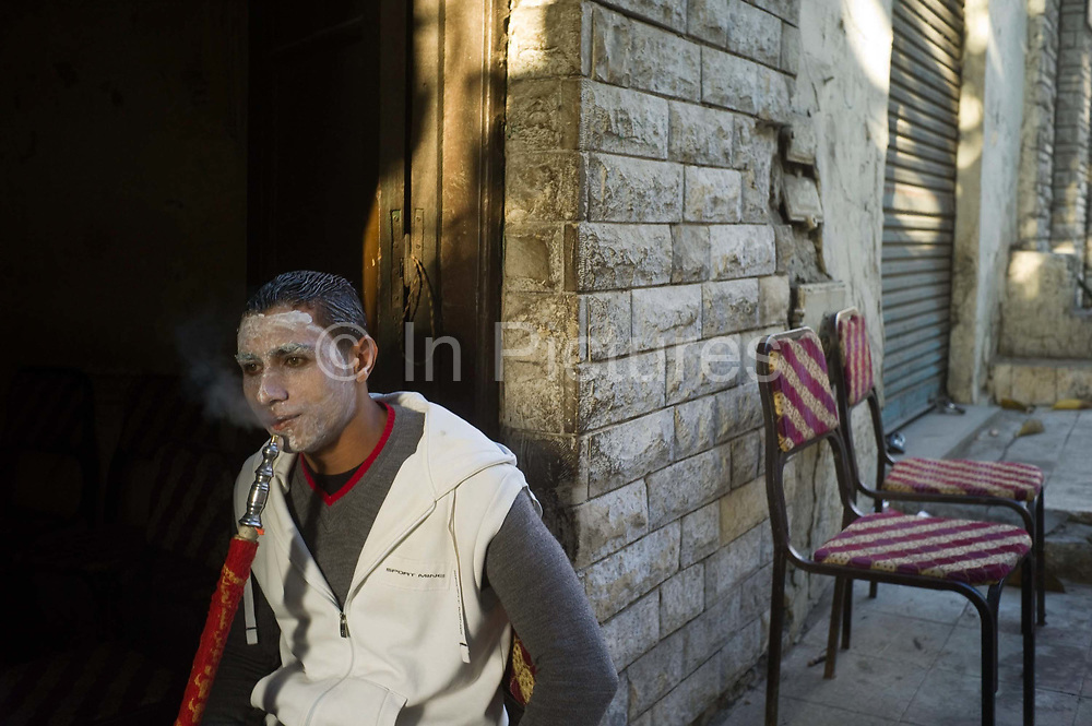 A young man smokes a shish pipe in a coffeshop or ahwa whilst wearing a face pack so that he can look at his best for his wedding in the evening. Cairo, Egypt