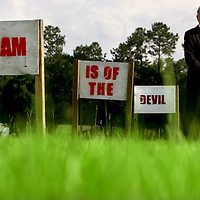 """GAINESVILLE, FL -- August 18, 2010 -- Pastor Terry Jones poses for a portrait with signs along the road that state """"Islam is of the Devil"""" at the Dove World Outreach Center in Gainesville, Fla., on Wednesday, August 18, 2010.  The signs have been replaced multiple times after vandalism.  The church is planning on burning multiple copies of the Koran on the anniversary of the September 11th terrorist attacks.  (Chip Litherland for The New York Times)"""