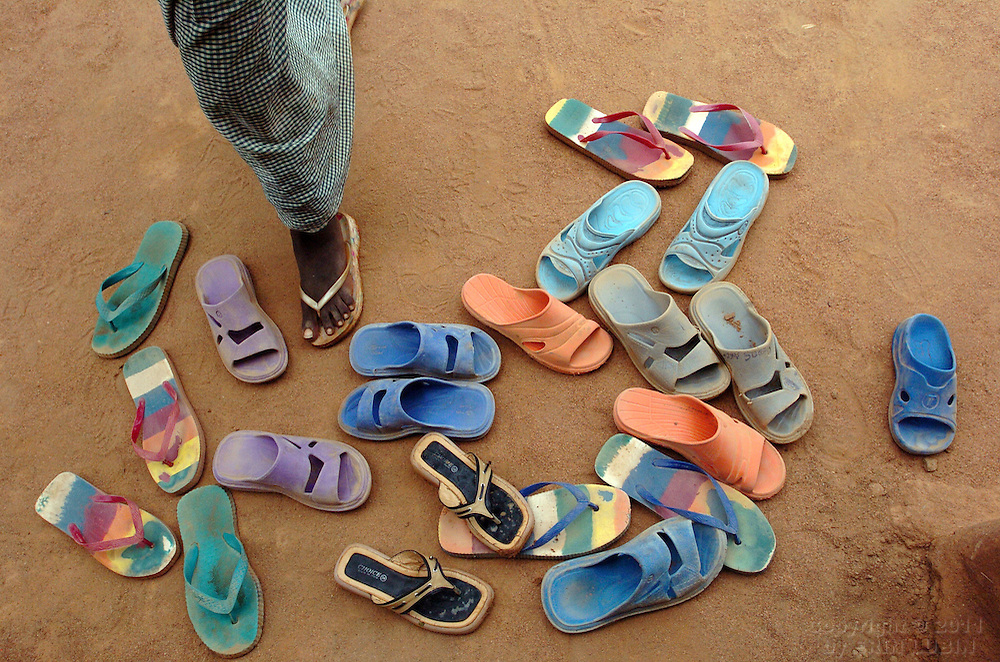 A child walks through a pile of sandals outside the Gambella community Baptist Church at Ifo Refugee Camp in Dadaab, Kenya September 15, 2006. ..Photograph by Erin Lubin