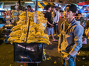 "21 DECEMBER 2015 - BANGKOK, THAILAND:  A marigold vendor on the street in front of Pak Khlong Talat, also called the Flower Market. The market has been a Bangkok landmark for more than 50 years and is the largest wholesale flower market in Bangkok. A recent renovation resulted in many stalls being closed to make room for chain restaurants to attract tourists. Now Bangkok city officials are threatening to evict sidewalk vendors who line the outside of the market. Evicting the sidewalk vendors is a part of a citywide effort to ""clean up"" Bangkok.      PHOTO BY JACK KURTZ"