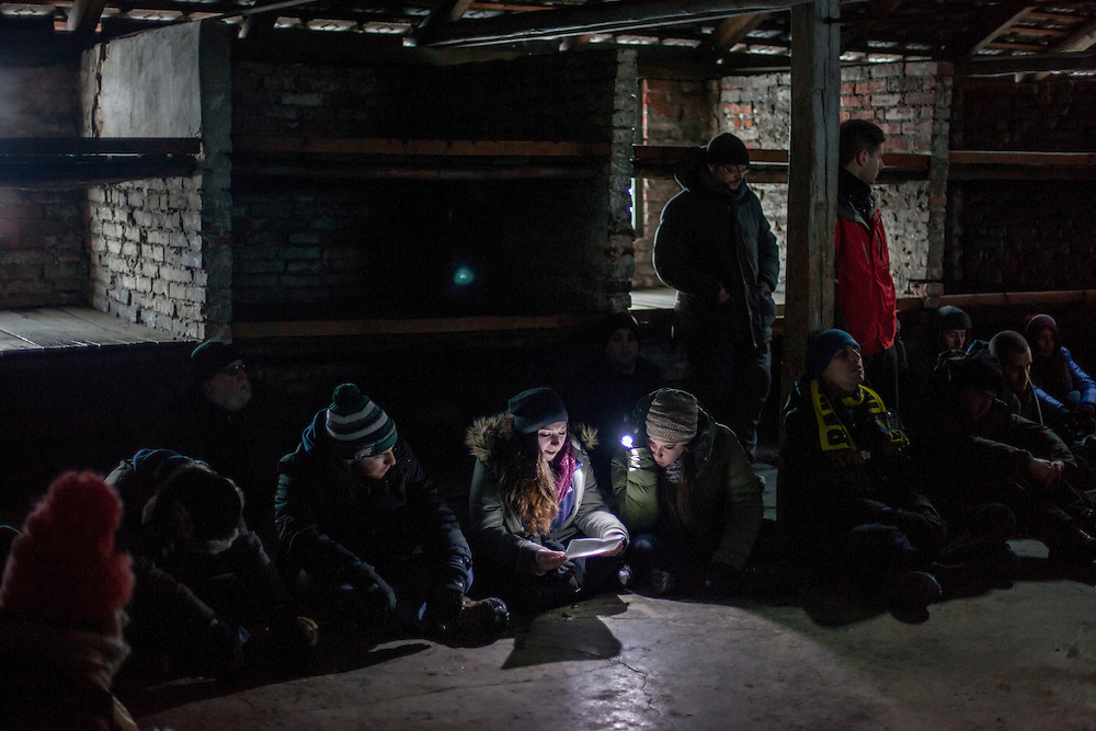 Young visitors sitting on the floor in one of the former prisoner brick barracks at the Auschwitz-Birkenau Nazi concentration camp close to Krakow in Poland. A woman is reading an eyewitness account of a former prisoner with the help of a torch. After a while she can not continue reading and starts to cry, she is passing the paper to somebody else who reads further. It is estimated that between 1.1 and 1.5 million Jews, Poles, Roma and others were killed in Auschwitz during the Holocaust between 1940-1945. The 27th of January 2015 is the 70th anniversary of the liberation of Auschwitz.
