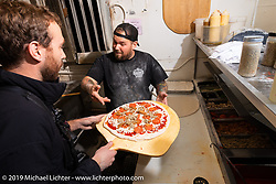 Joe Mialki teaches Sean Lichter how to make pizza at Giuseppe's Steel City Pizza restaurant during Daytona Bike Week. South Daytona Beach, FL. USA. Monday March 12, 2018. Photography ©2018 Michael Lichter.