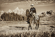 A Wrangler Passes in Front of the Grand near Hedrick Pond in Grand Teton National Park.