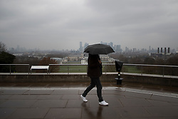 © Licensed to London News Pictures. 10/03/2021. London, UK.  A member of the public shelters under an umbrella as he walks in a wet and windy Greenwich Park . A yellow weather warning for wind is in place in parts of the UK. Photo credit: George Cracknell Wright/LNP