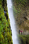 Hikers marvel at Tunnel Falls from the Eagle Creek Trail, cut into the basalt cliff behind the waterfall, in Columbia River Gorge National Scenic Area, Oregon.