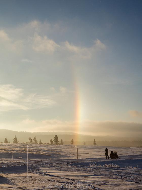 Snowmobiler watching a sundog, Yellowstone National Park