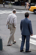 two differently dressed business people waiting to cross the street NYC