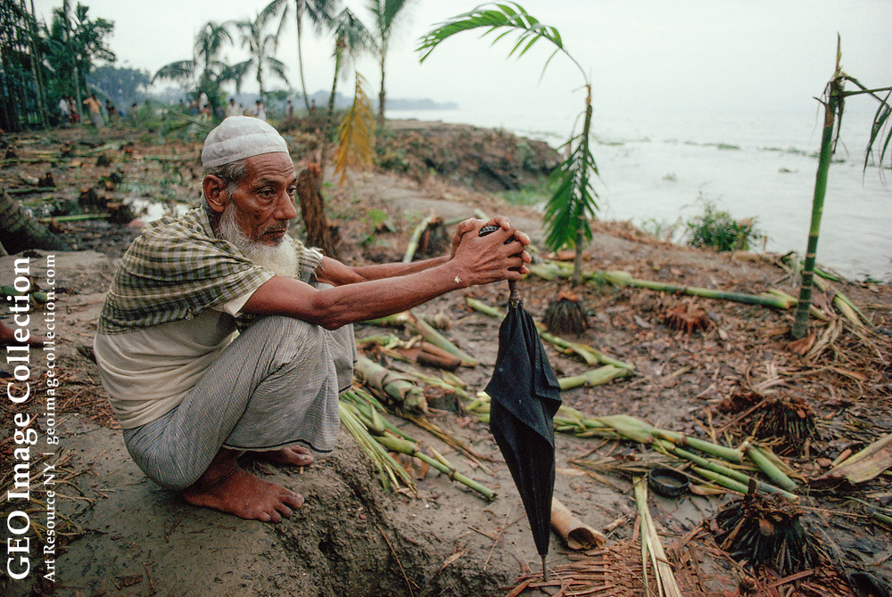 Mono Mia, 55, sits on the foundation of his house carried away by monsoon flood waters of the Meghna River.