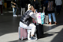 © Licensed to London News Pictures. 04/05/2019. London, UK. A woman sitting on her suitcase at Kings Cross rail station as she waits to travel for the May Bank holiday weekend. According to the Met Office many parts of the UK will have snow, hail and thunder for the weekend and the temperature for the May Bank holiday could drop to as low as -6 degrees celsius. Photo credit: Dinendra Haria/LNP