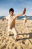 A group of asian people practice tai chi on a beach by early morning. Quy Nhon, Vietnam, Southeast Asia