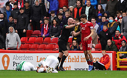 Referee Bobby Madden pushes away Aberdeen's Calvin Ramsay after challenges on Celtic players during the cinch Premiership match at Pittodrie Stadium, Aberdeen. Picture date: Sunday October 3, 2021.