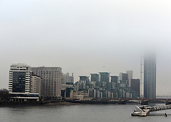 © Licensed to London News Pictures. 16/01/2013. London, UK A view of the scene shrouded in fog see from Lambeth Bridge. A damaged crane is seen hanging from the side of the St George's Wharf development near Vauxhall in in London today (16/01/13) after a being hit by a helicopter, which then crashed.  Photo credit : Stephen Simpson/LNP
