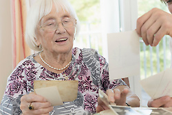 Senior woman watching photos with caretaker in rest home, Bavaria, Germany