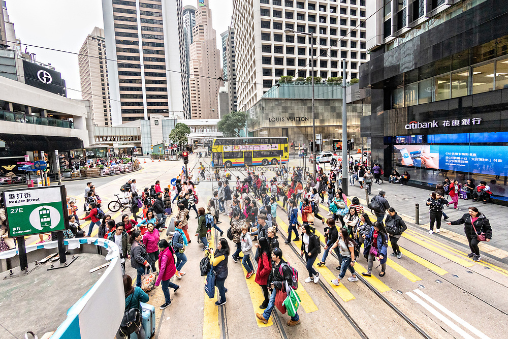 Crowds of pedestrians cross Des Voeux Road in the central district of Hong Kong.