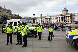 London, UK. 16 October, 2019. Police officers and vehicles parked on Trafalgar Square close to hundreds of climate activists from Extinction Rebellion defying the Metropolitan Police prohibition on Extinction Rebellion Autumn Uprising protests throughout London under Section 14 of the Public Order Act 1986 by attending a Right to Protest assembly. The Metropolitan Police made arrests, including Green Party co-leader Jonathan Bartley and Guardian journalist George Monbiot, after a group of protesters sat down in the road in Whitehall.