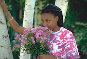 African exchange student age 17 sniffing purple flowers by birch tree.  St Paul Minnesota USA