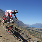 Zach Baker from Waimauku in action during the NZBNZ South Island Downhill Cup mountain bike downhill series held on The Remarkables face with a stunning backdrop of the Wakatipu Basin. 150 riders took part in the two day event.  Queenstown, Otago, New Zealand. 9th January 2012. Photo Tim Clayton