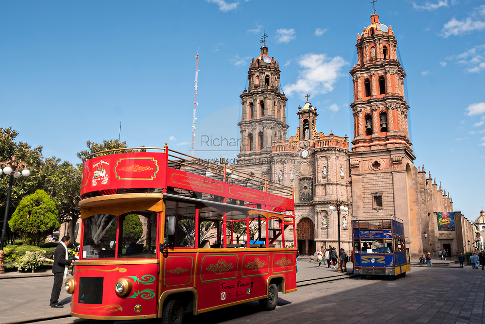 A quaint double decked tour bus passes the baroque facade of the Cathedral of San Luis Potosi in the historic center on the Plaza De Armas in the state capital of San Luis Potosi, Mexico. Also known as the San Luis Potosi Metropolitan Cathedral, it is consider the most important monument in the state and the first Baroque style building constructed in 1670 on the site of a parish church first built in 1593.